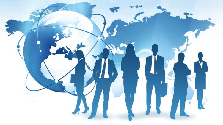 Hommes et femmes d'affaires debout devant une carte du monde