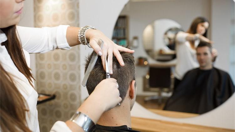 coiffeuse réalisant une coupe de cheveux