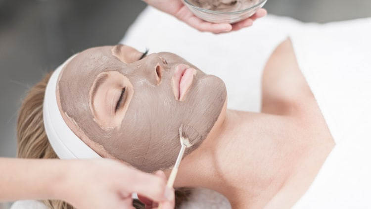 Jeune femme masque visage cosméticienne