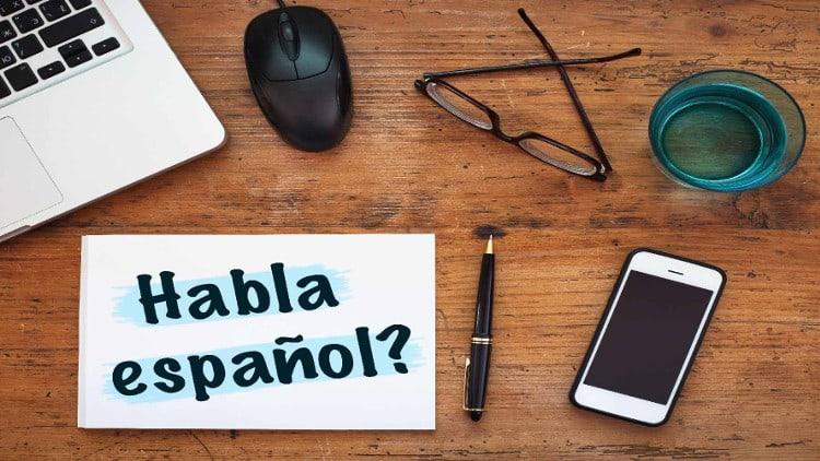 Bureau avec téléphone et portable et cahier habla español