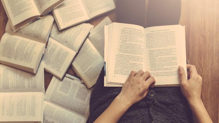 Livres étalés à terre et mains tenant un livre