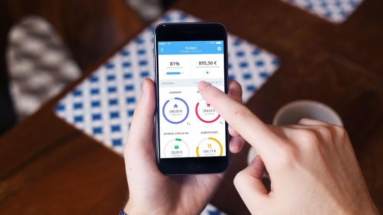 main qui tient un téléphone avec l'application bankin