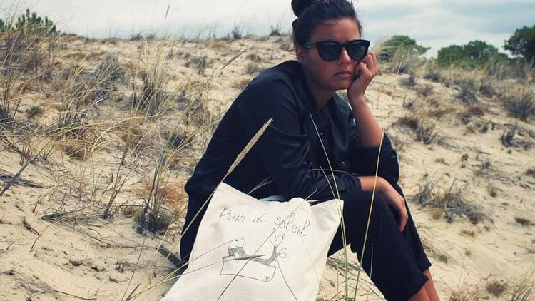 femme sur une plage qui porte un tote bag